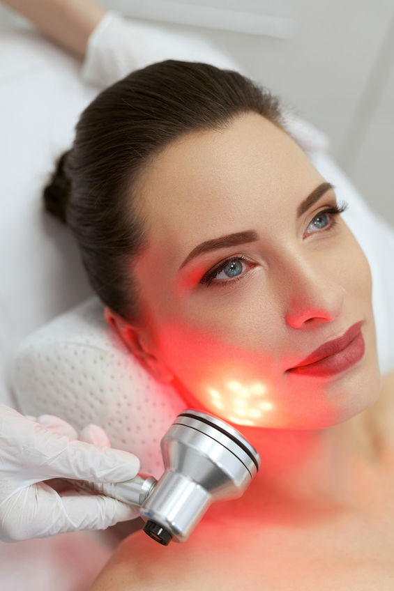 Facial Cosmetology. Woman On Red Light Face Skin Care Treatment At Beauty Spa Center. High Resolution
